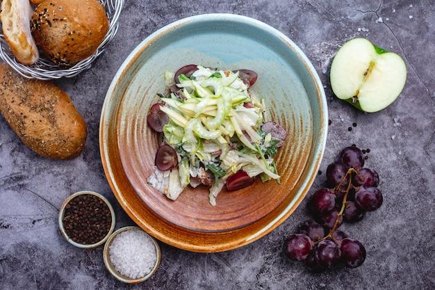 Vista superior da tigela de salada de maçã com aipo uísque alface foguete e atum