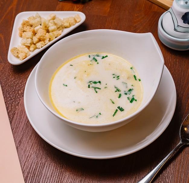 Vista superior da tigela de sopa de galinha cremosa, guarnecida com salsa, servida com recheio de pão
