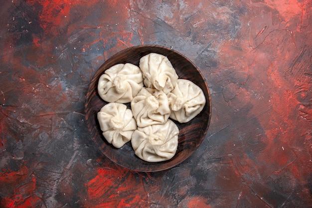 Vista superior da tigela khinkali de longe do apetitoso khinkali na mesa cinza-avermelhada