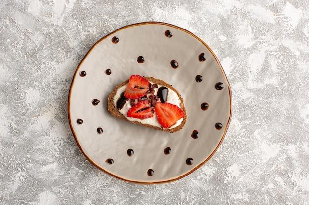 Vista superior da torrada com morango e creme de leite dentro do prato marrom na superfície cinza clara