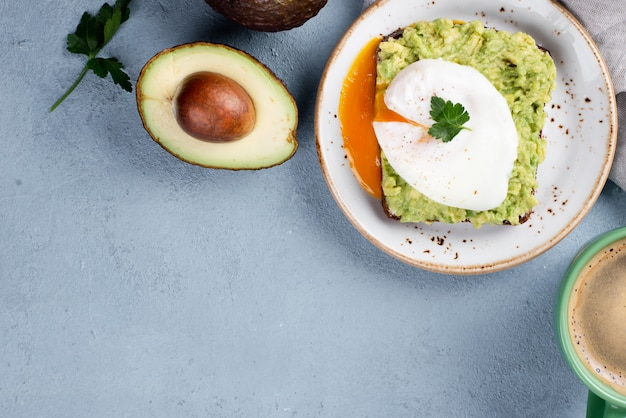 Vista superior da torrada de abacate no prato com ovo escalfado e xícara de café