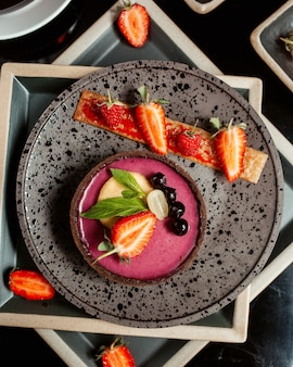 Vista superior da torta de berry, decorada com uva e pêssego de morango