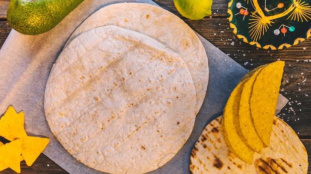 Vista superior da tortilla mexicana e saborosos nachos na mesa de madeira