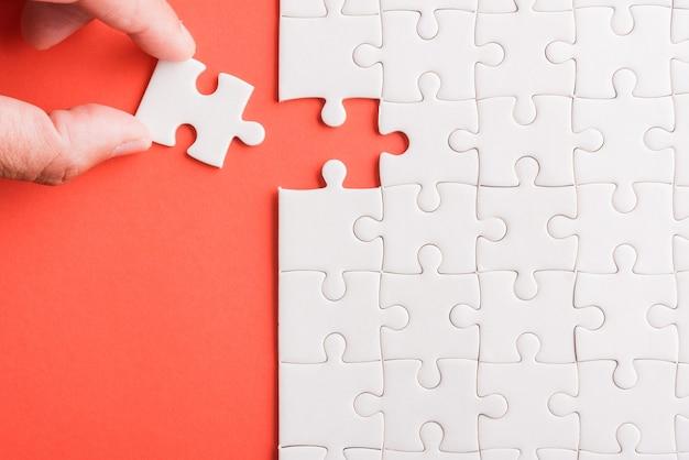 Vista superior da última peça do jogo de quebra-cabeça de papel branco segurando as últimas peças colocadas para resolver o problema missão completa