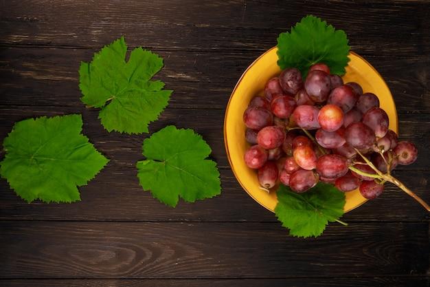 Vista superior da uva doce fresca em um prato e folhas de uva verde na mesa de madeira escura