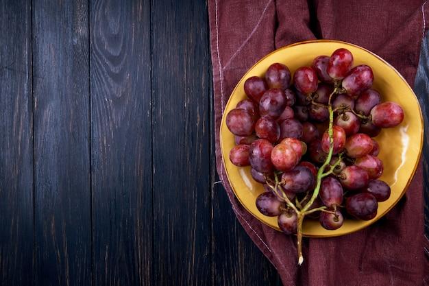 Vista superior da uva doce fresca em um prato na mesa de madeira escura com espaço de cópia