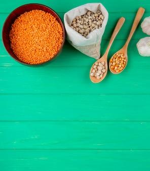 Vista superior da variedade de cereais e leguminosas - grãos de grão de bico de feijão branco e lentilhas vermelhas e arroz na superfície de madeira verde com espaço de cópia