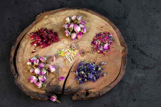Vista superior da variedade de flores secas e chá de rosas em uma placa de madeira em preto