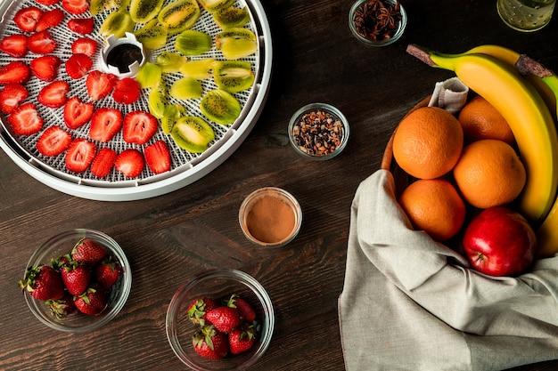 Vista superior da variedade de frutas frescas na mesa da cozinha de madeira, incluindo kiwi fatiado e morangos na bandeja do secador e especiarias aromáticas
