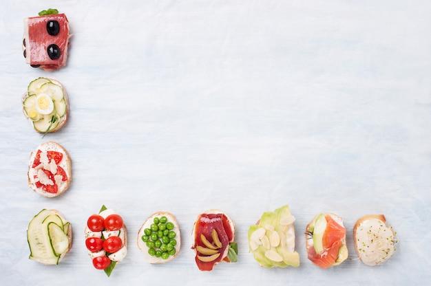 Vista superior da variedade de sanduíches saudáveis em papel pergaminho, com espaço para texto.