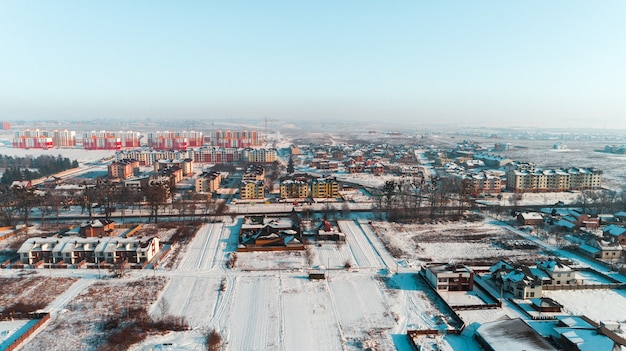 Vista superior da vila de inverno com estradas e casas cobertas de neve. vista aérea da paisagem