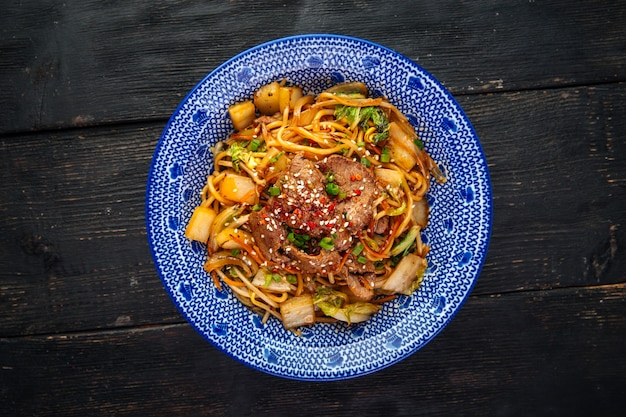 Vista superior da wok de macarrão de jakisoba com carne asiática na mesa de madeira escura