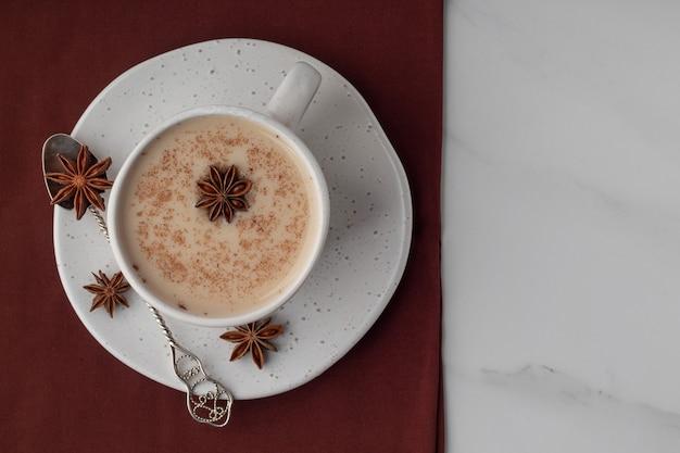 Vista superior da xícara com chá indiano masala chai e especiarias na mesa de mármore, espaço para texto