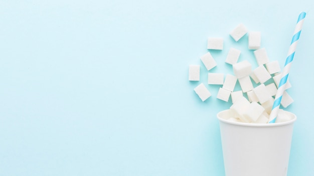Vista superior da xícara com cubos de açúcar e canudo