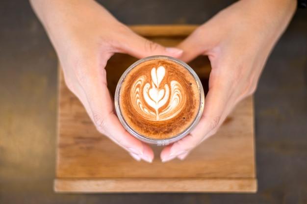 Vista superior da xícara de arte com leite quente no fundo da mesa de madeira