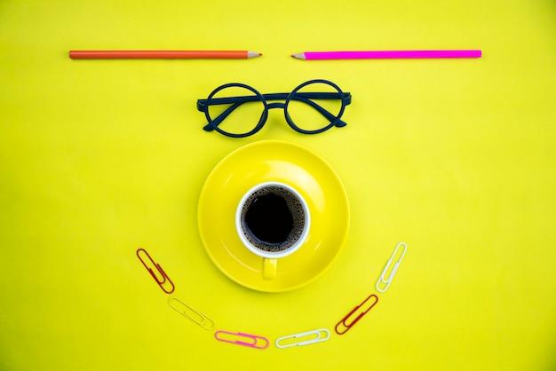 Vista superior da xícara de café amarelo com óculos de professor e lápis colorido