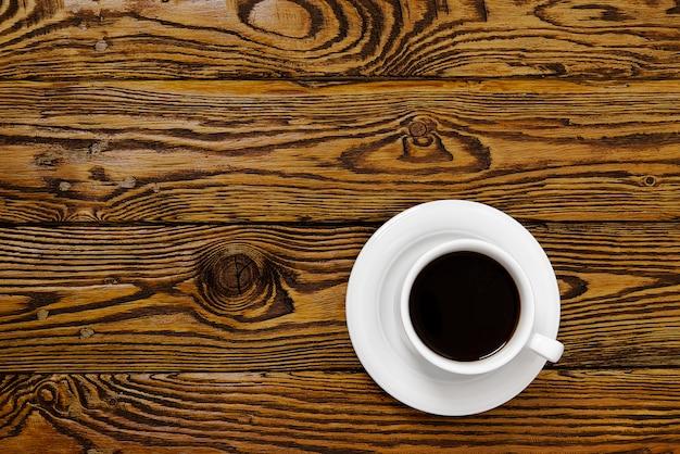 Vista superior da xícara de café branco na mesa de madeira velha. bebida aromática de café em copo branco na mesa de madeira marrom