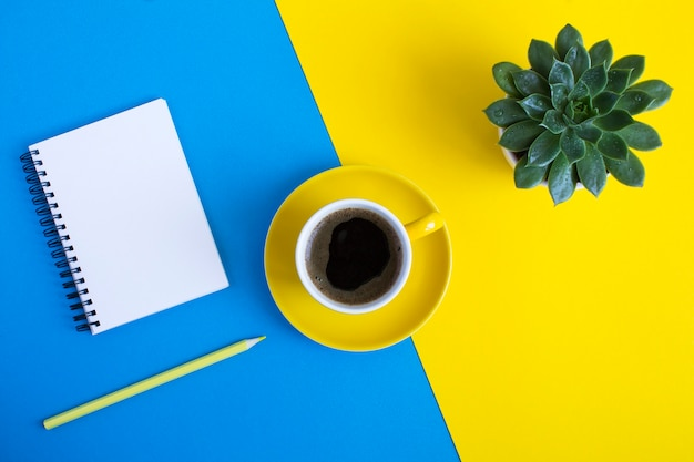 Vista superior da xícara de café, cacto, lápis amarelo e bloco de notas para escrever