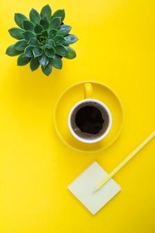 Vista superior da xícara de café, cacto, lápis amarelo e papel para escrever. postura plana da mesa de trabalho. copie o espaço.