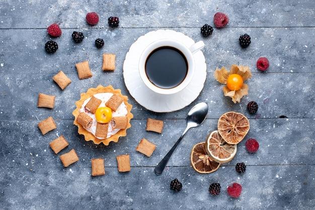 Vista superior da xícara de café com almofada de bolo cremoso formando biscoitos junto com frutas na mesa cinza, cor da foto do biscoito de baga