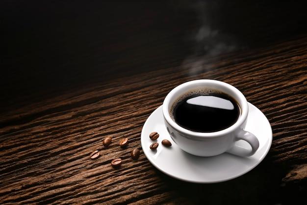 Vista superior da xícara de café com fumaça e grãos de café na velha mesa de madeira
