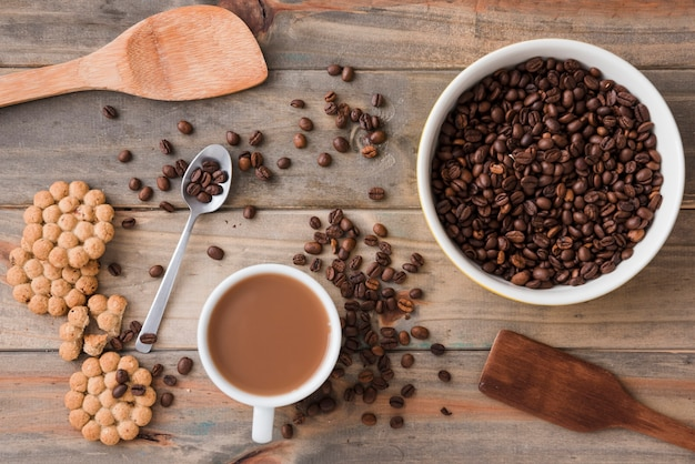 Vista superior da xícara de café com grãos e colheres