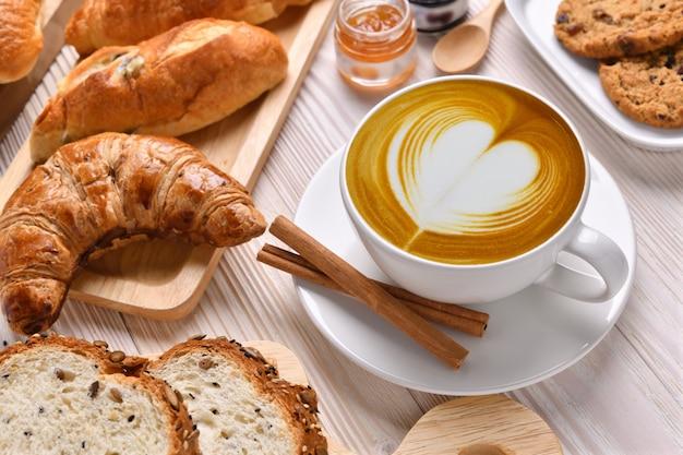 Vista superior da xícara de café com leite com pães ou pão, croissant e padaria na mesa de madeira branca