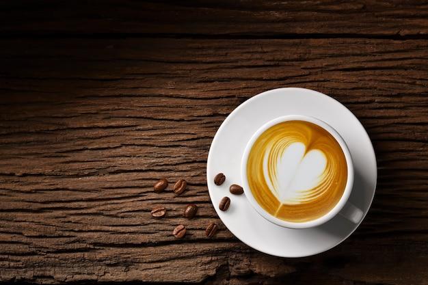 Vista superior da xícara de café com leite em formato de coração e grãos de café na velha mesa de madeira