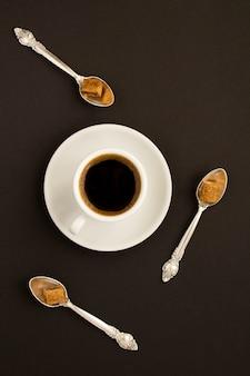 Vista superior da xícara de café e colheres com açúcar na mesa preta. fechar-se.