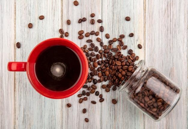 Vista superior da xícara de café e grãos de café derramando da jarra de vidro no fundo de madeira