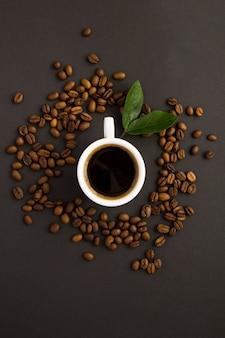 Vista superior da xícara de café e grãos de café na mesa preta. fechar-se.