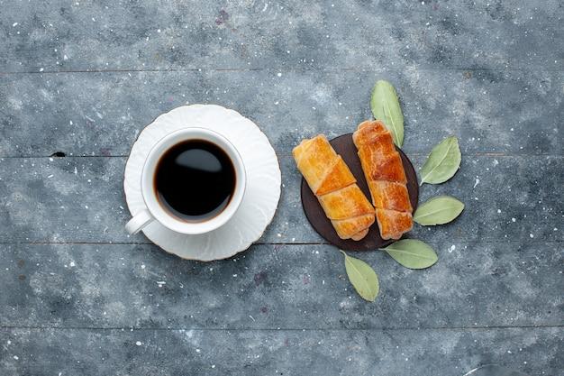Vista superior da xícara de café junto com pulseiras deliciosas e doces em madeira cinza, bolo de confeitaria doce