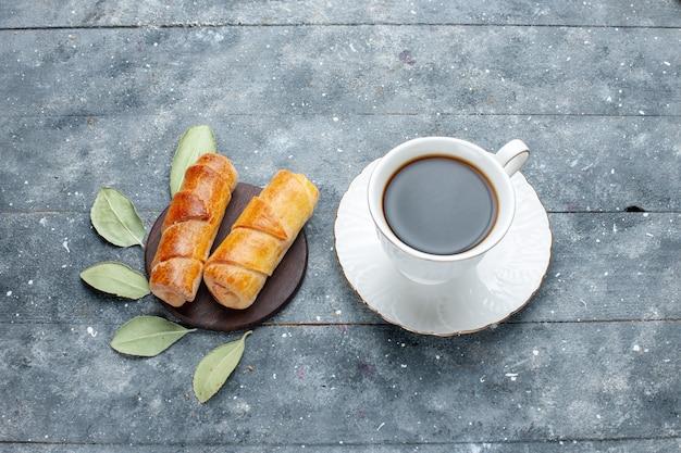 Vista superior da xícara de café junto com pulseiras deliciosas e doces em um bolo de confeitaria de madeira cinza