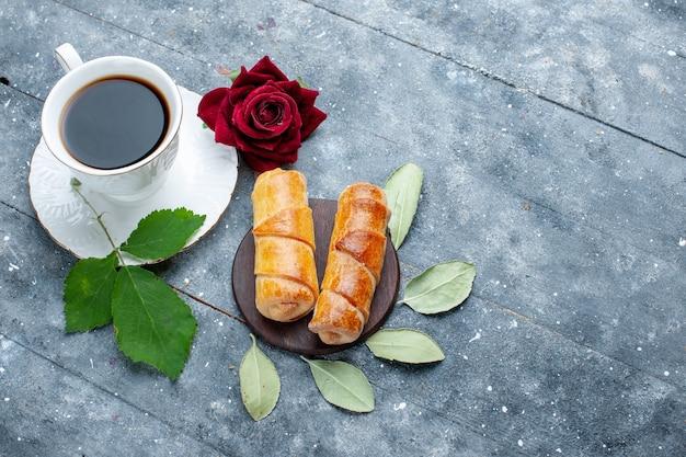 Vista superior da xícara de café junto com pulseiras deliciosas e rosa vermelha em madeira cinza, bolo de confeitaria doce
