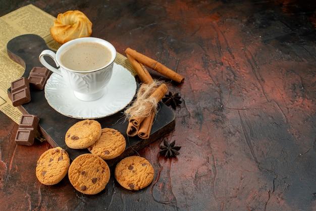 Vista superior da xícara de café na tábua de madeira, biscoitos, lima e canela, barras de chocolate no lado direito na superfície escura