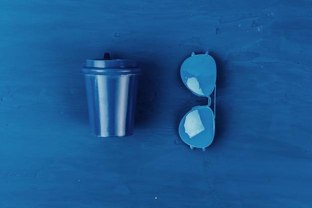 Vista superior da xícara de café para viagem com óculos de sol aviador em fundo azul clássico
