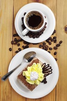 Vista superior da xícara de café quente e prato com bolo delicioso