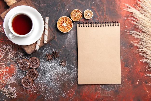 Vista superior da xícara de chá com biscoitos na mesa escura cerimônia escura de biscoito