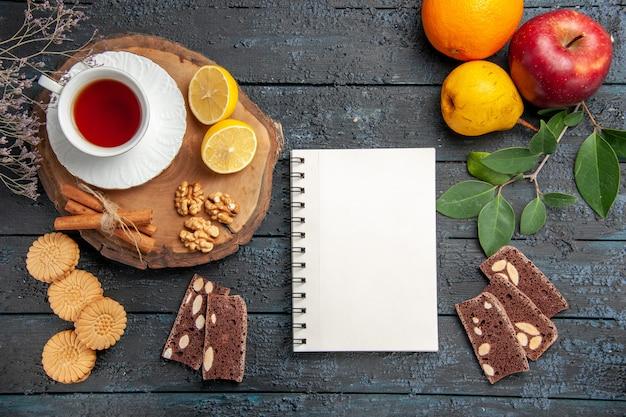 Vista superior da xícara de chá com limão e doces na mesa escura