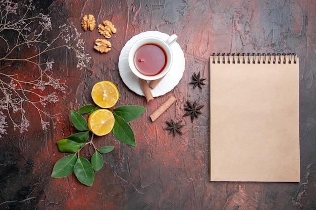Vista superior da xícara de chá com limão na foto escura dos frutos do chá da mesa escura