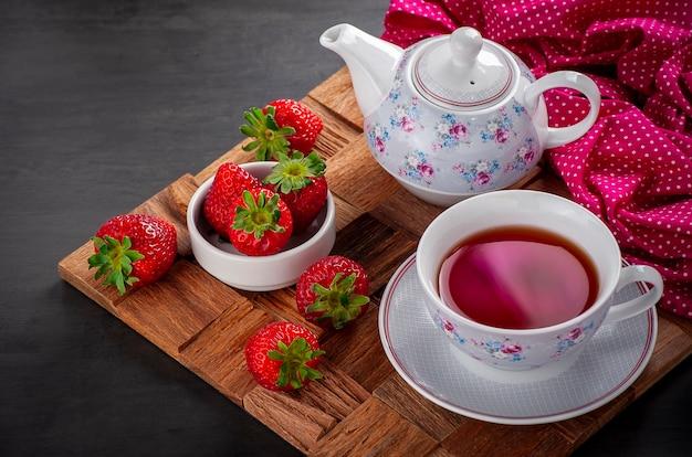 Vista superior da xícara de chá com morangos inteiros