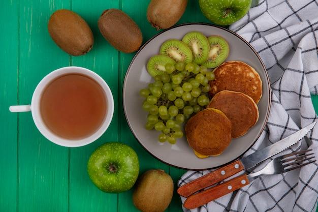 Vista superior da xícara de chá com uvas verdes kiwi e panquecas em um prato com uma faca e um garfo em uma toalha quadriculada em um fundo verde