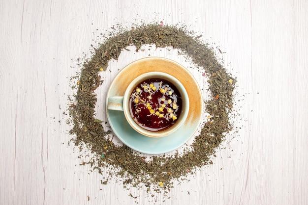 Vista superior da xícara de chá de ervas e ervas ao redor na mesa branca