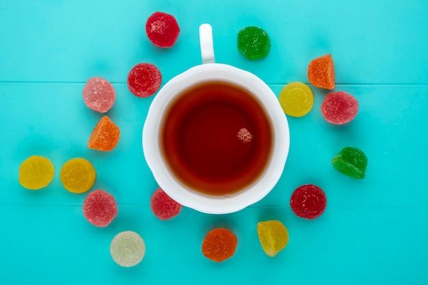 Vista superior da xícara de chá e marmeladas no fundo azul