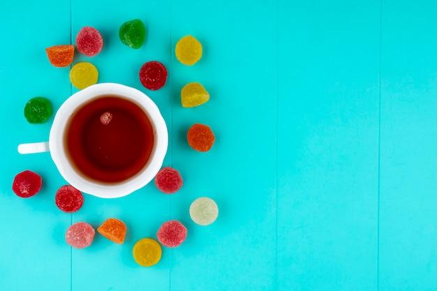 Vista superior da xícara de chá e marmeladas sobre fundo azul, com espaço de cópia
