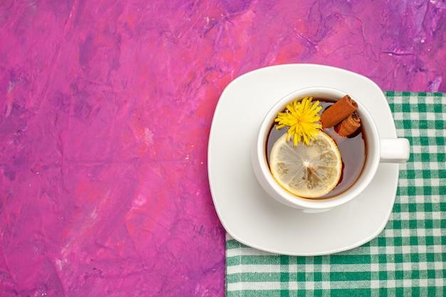 Vista superior da xícara de chá em toalha verde despojada com limão e canela de lima em rosa