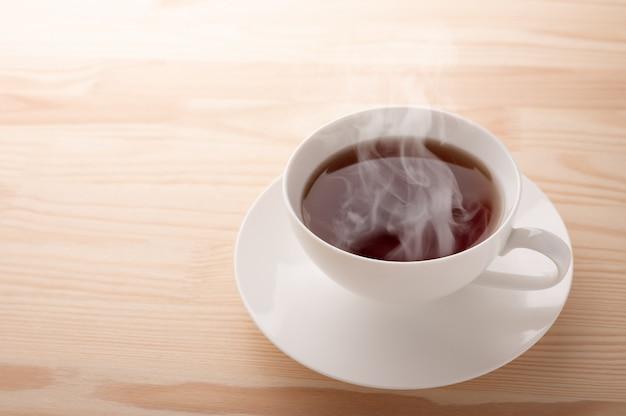 Vista superior da xícara de chá. xícara chinesa de porcelana branca de chá preto e pires no fundo da mesa de madeira vintage.