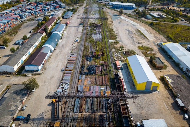 Vista superior da zona industrial: trilhos, garagens, armazéns, contêineres para armazenamento de mercadorias.