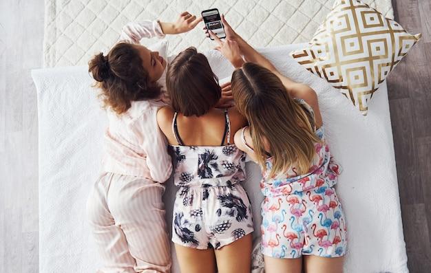 Vista superior das amigas felizes que estavam deitada na cama e se divertindo na festa do pijama no quarto.