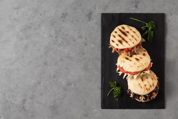Vista superior das arepas com carne e tomate